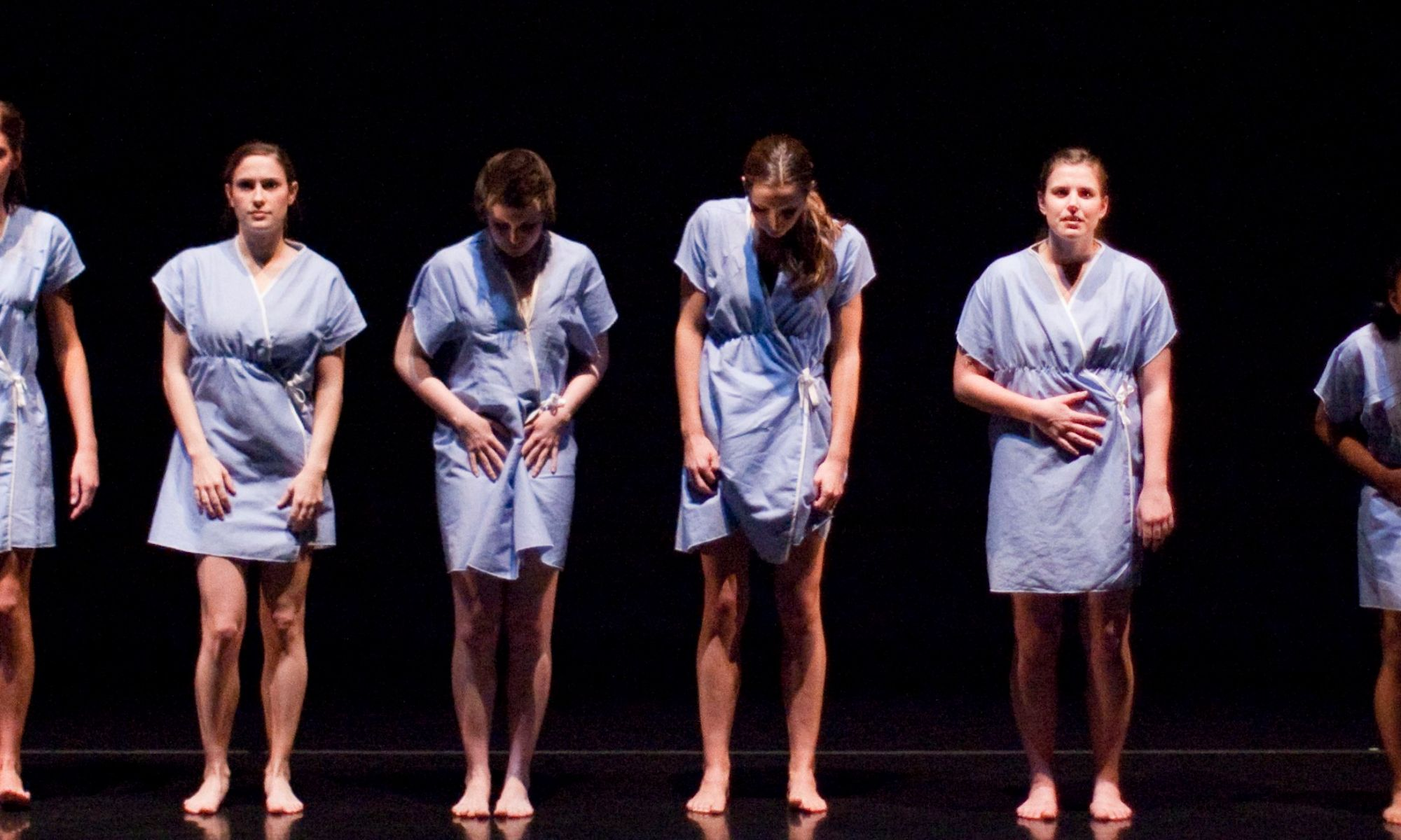 6 women standing, wearing blue hospital gowns, cringing and holding their bellies.